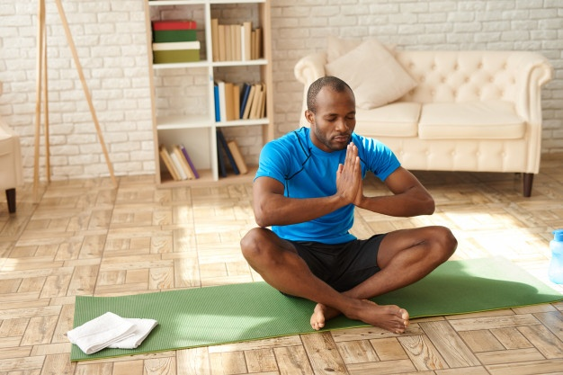 Man mediating at home to relieve stress